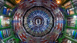 The photos shows the Hadron Collider at the center. There are metal and electronic parts coming out of the center, each band made of different materials coming out in concentric circles. At the edge is a green scaffolding for people to walk on it.
