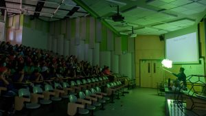 Green lit dark auditorium with students on the left, and a chemistry on the right.