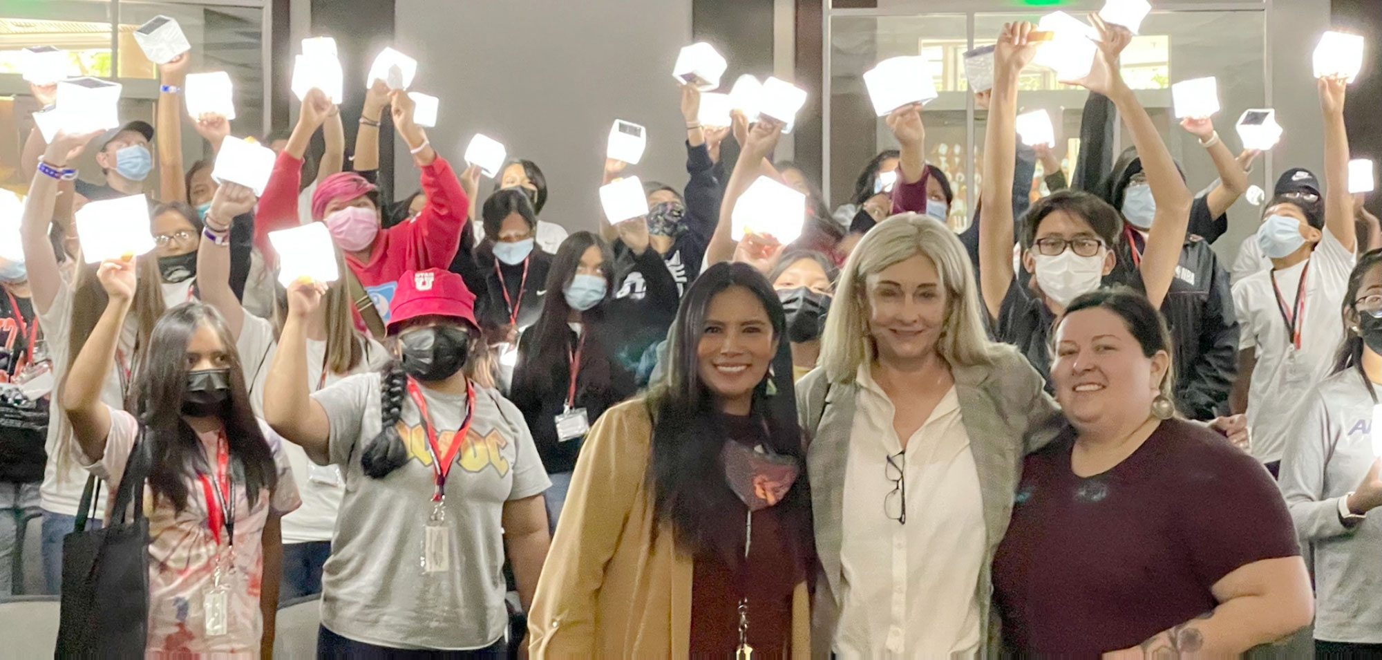 Three women stand in front of dozens of students who hold up illuminated cube lights in the background.