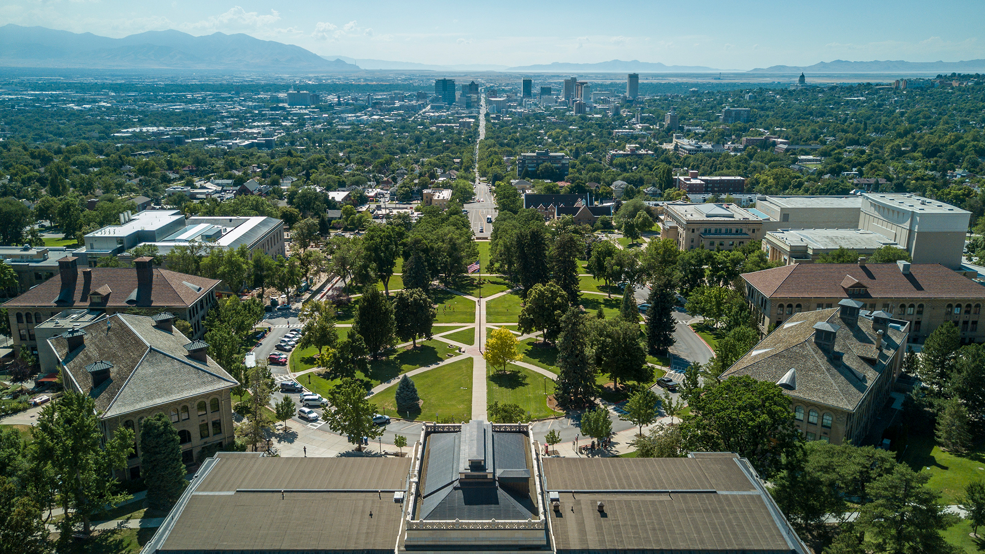 aerial photograph above the Park Building on the University of Utah campus facing west featuring downtown Salt Lake and mountains on the West Side.