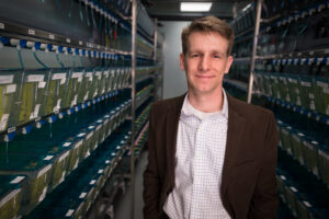 A man stands in a row of zebrafish enclosures.