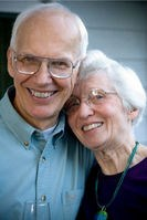 Bill, a man with white hair glasses and a blue shirt, hugs his wife Ruth, a woman with white hair, glasses, and black shirt and a blue necklace.