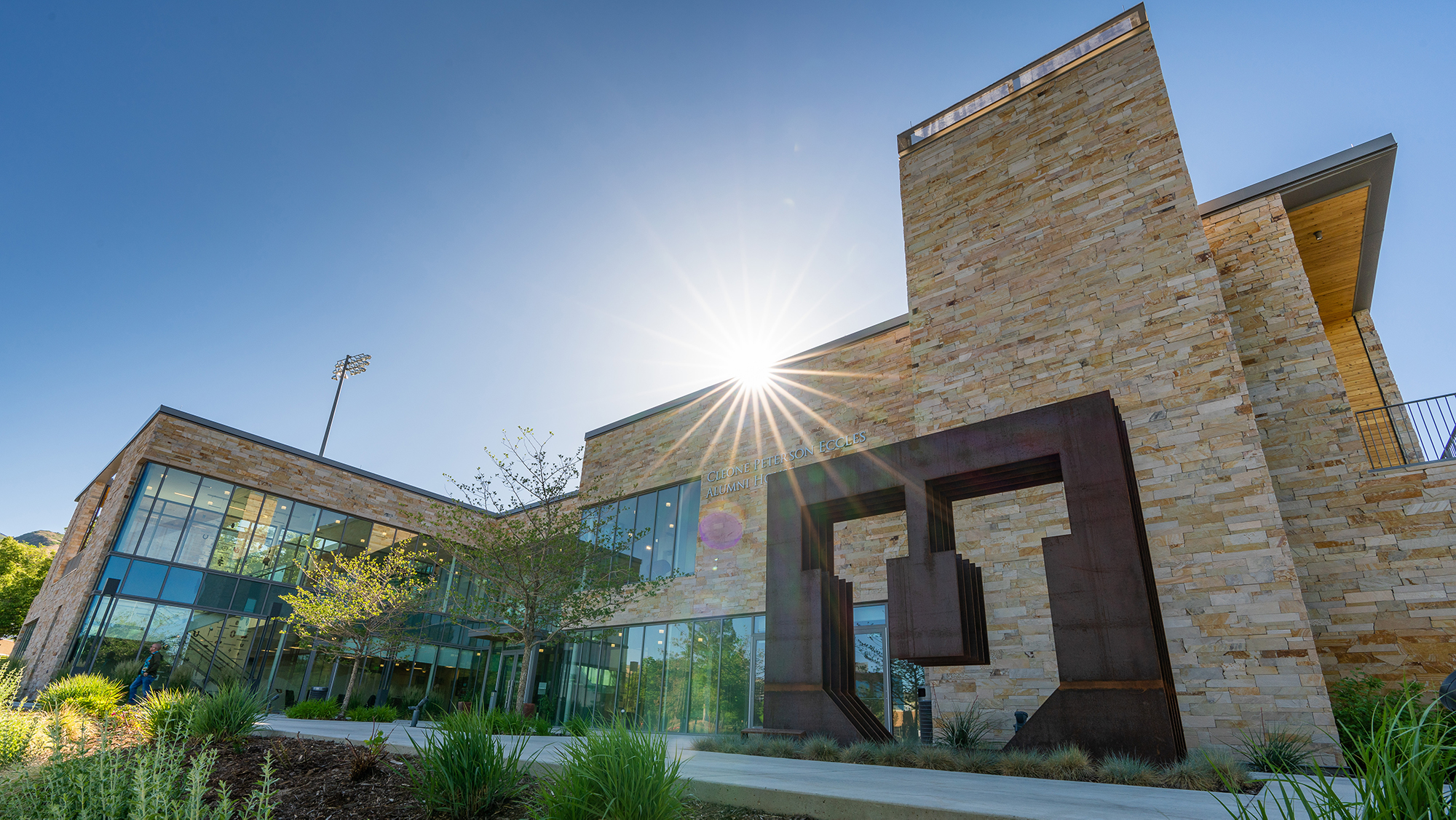Alumni building photo is taken from ground up with sun peaking over building and prominent Block U sculpture is out front of the building.