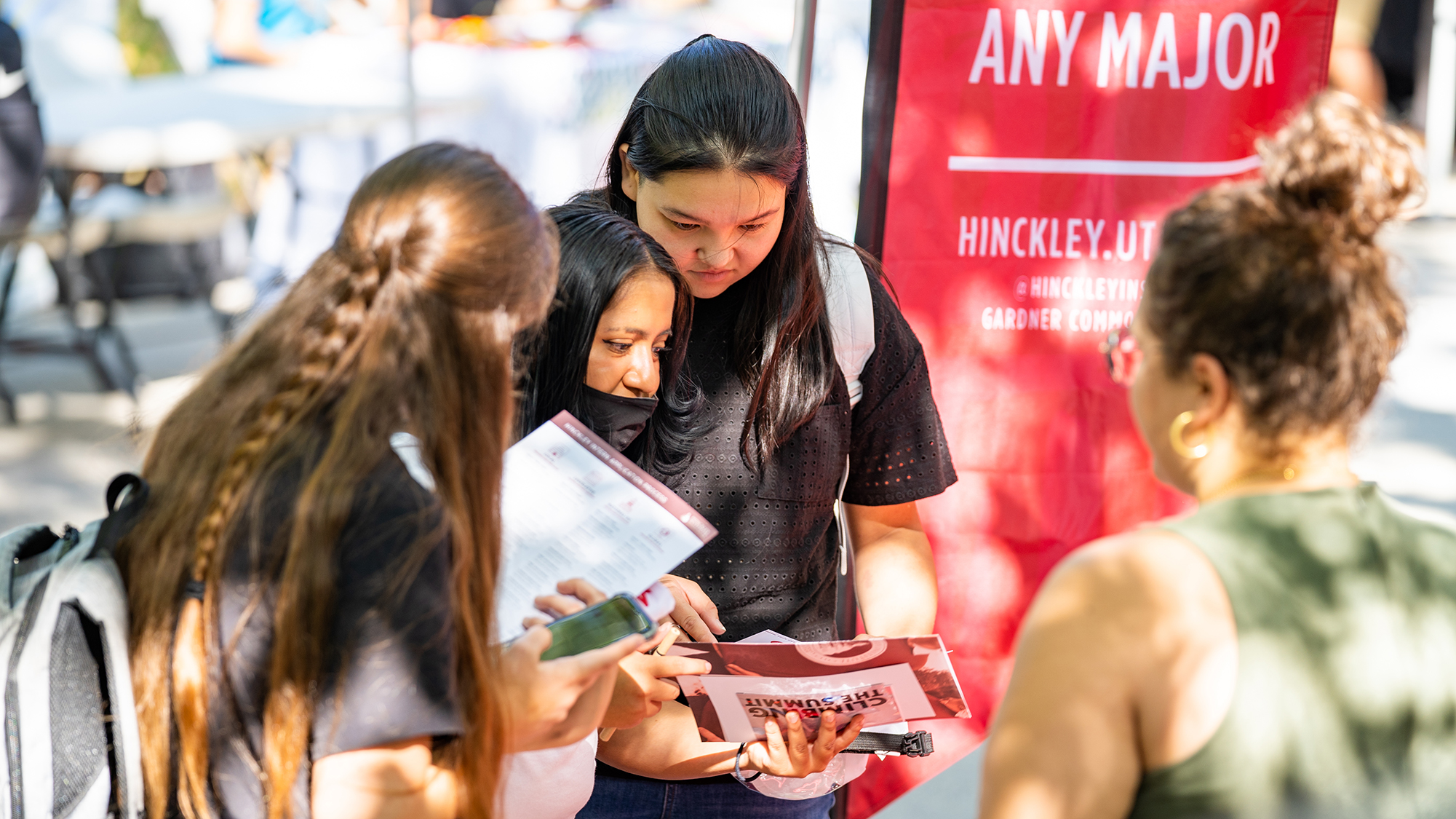 three University of Utah students look at flyers handed out by a staff member during a tabling event on campus.