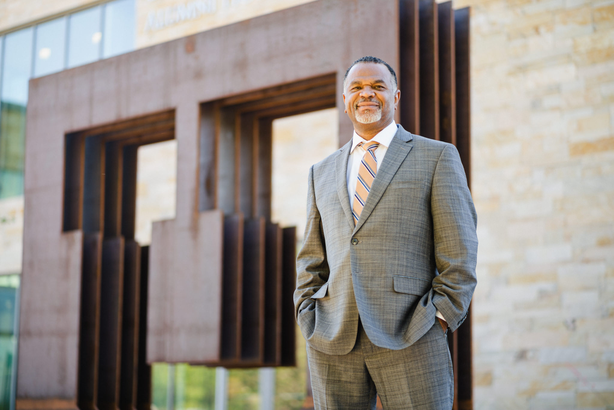 """Martell Teasley, Dean of the College of Social Work, poses in a suit with his hands in his pockets in front of a """"U"""" statue."""