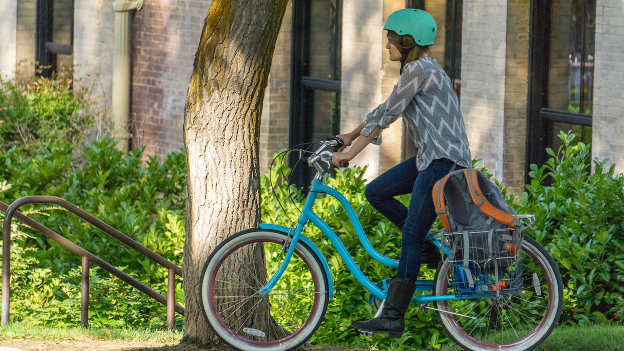 person on a teal bike with a teal helmet riding past a tree with green bushes in the background.