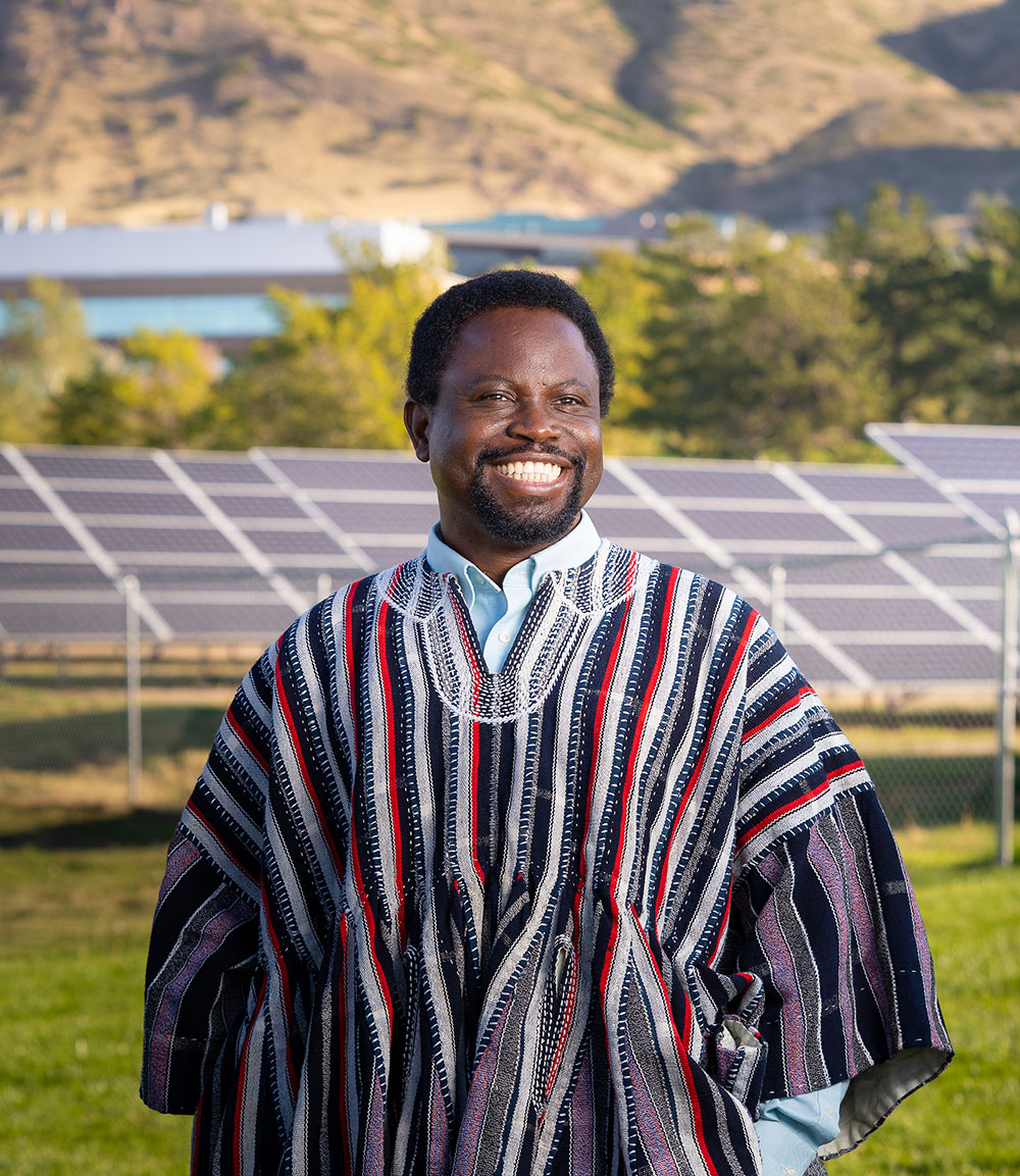 A Black man stands in front of an array of large solar panels against a mountain background. He is wearing a traditional shirt from northern Ghana. It's woven with vertical stripes of red, blue, purple, gray and white.