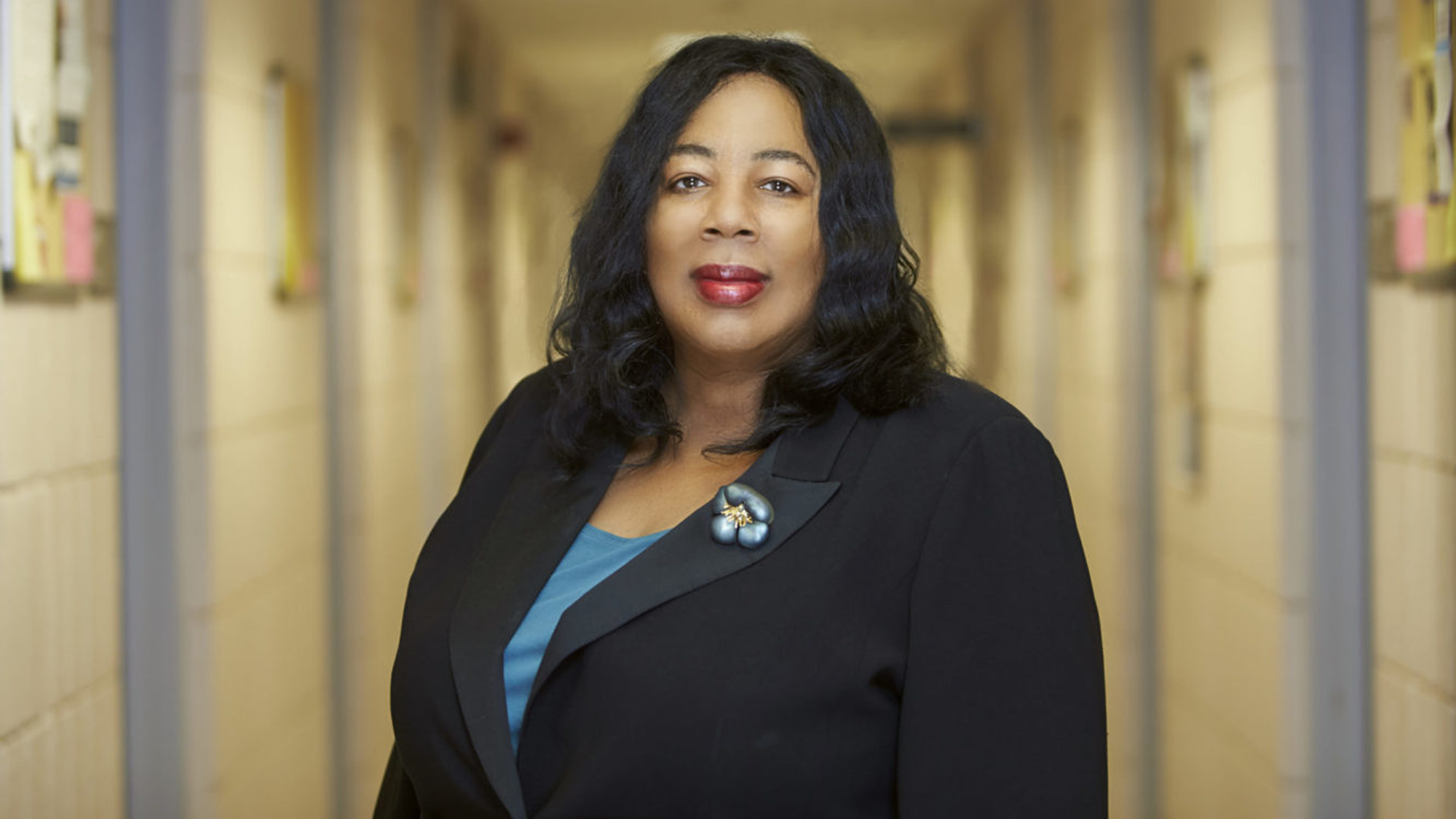 Headshot of Harriet Washington, a Black Woman with black hair down a few inches past her shoulders, wearing a dark blazer over a light blue shirt.