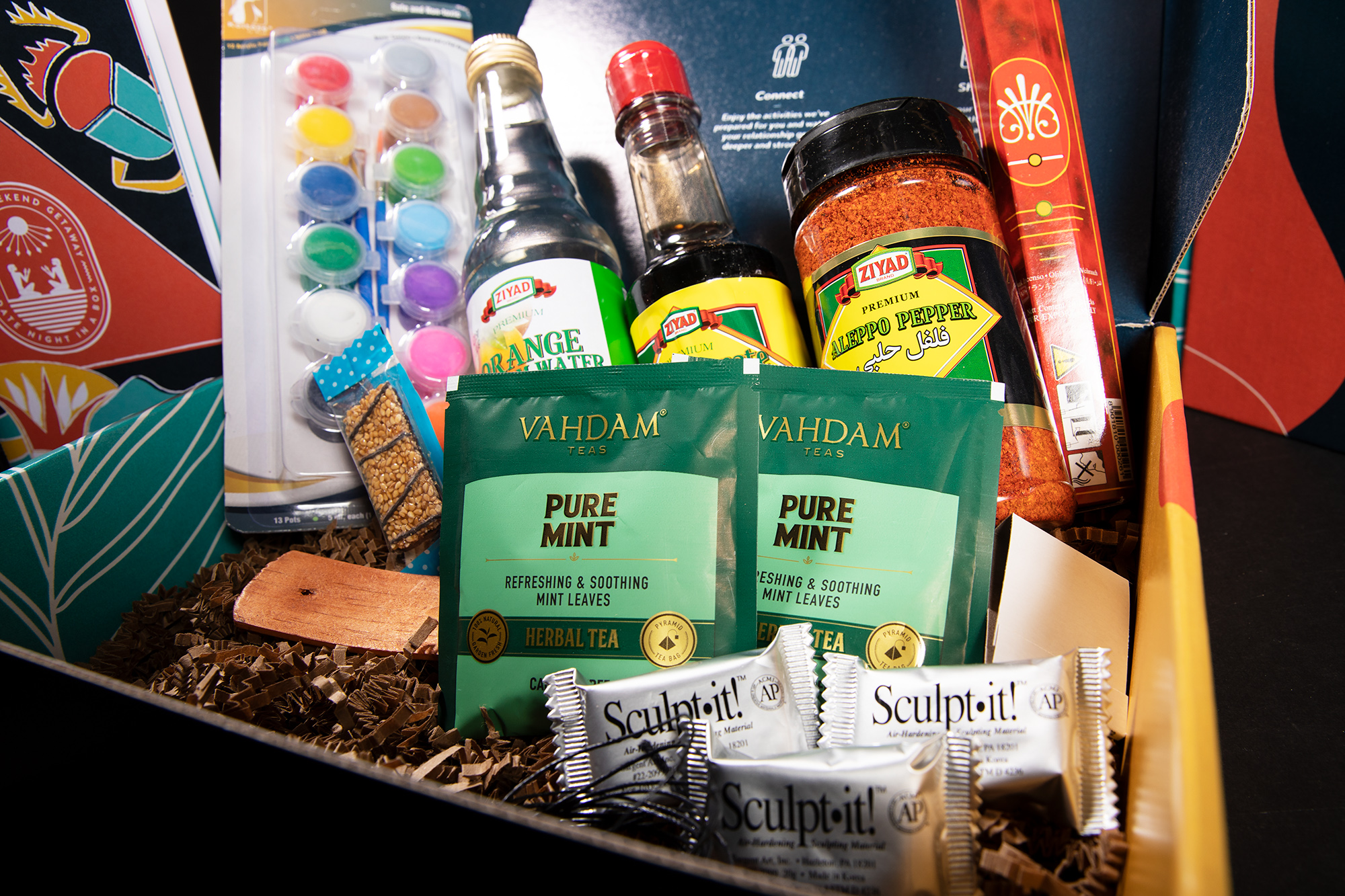 A basket full of goodies like sauces, chocolate, water              color paints and other seasonings for a date night.