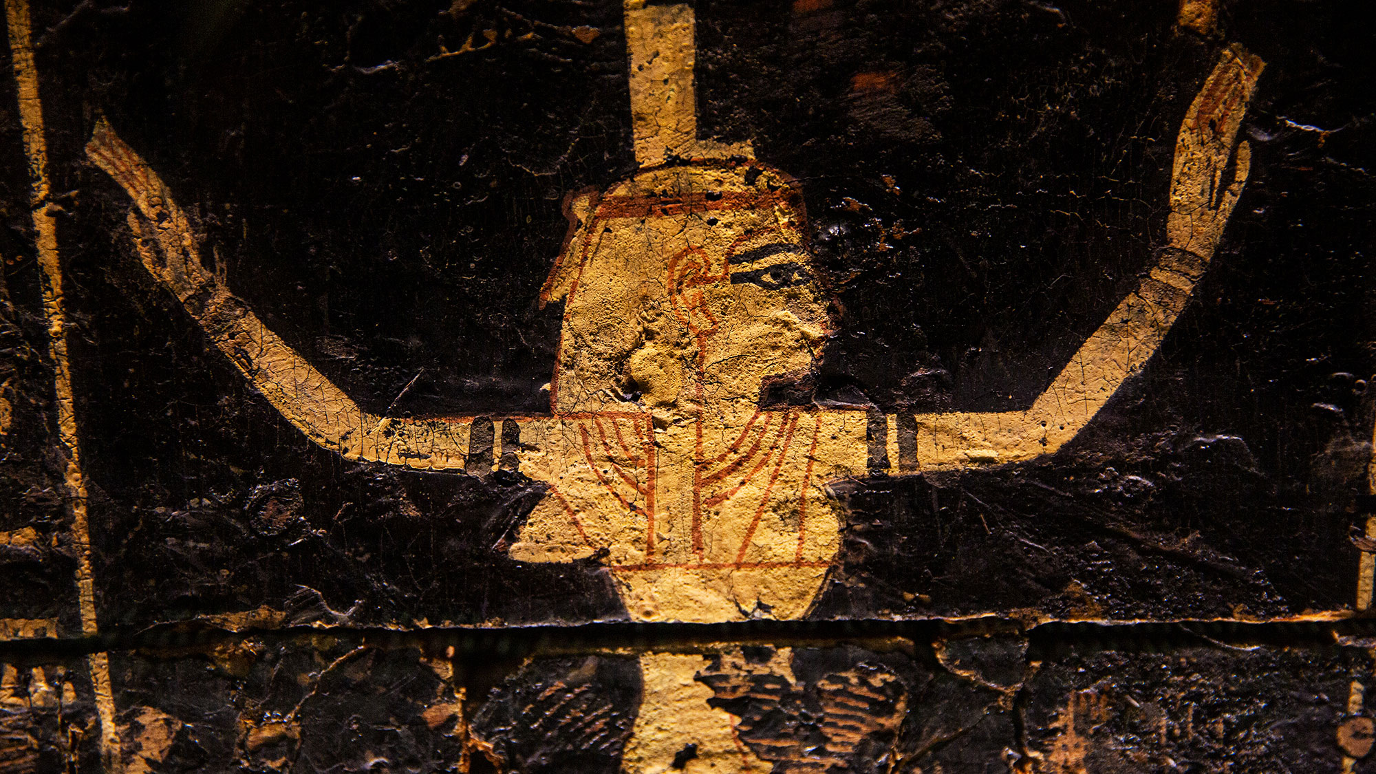 Egyptian art, with a woman in gold in a hieroglyphic style, with her arms raised high and her head looking left.
