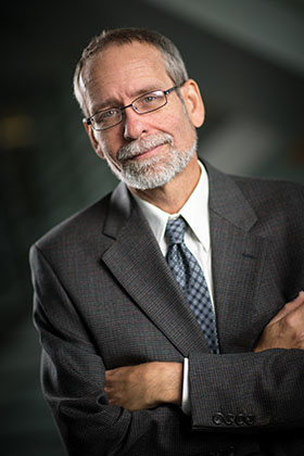A man with a gray goatee and mustache with wire rimmed glasses and a gray shirt against a gray background.
