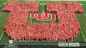 """hundreds of students wearing stand close together to form a block U on the University of Utah football field. bottom text reads, """"Class of 2025,"""" Office of Orientation and Transition."""