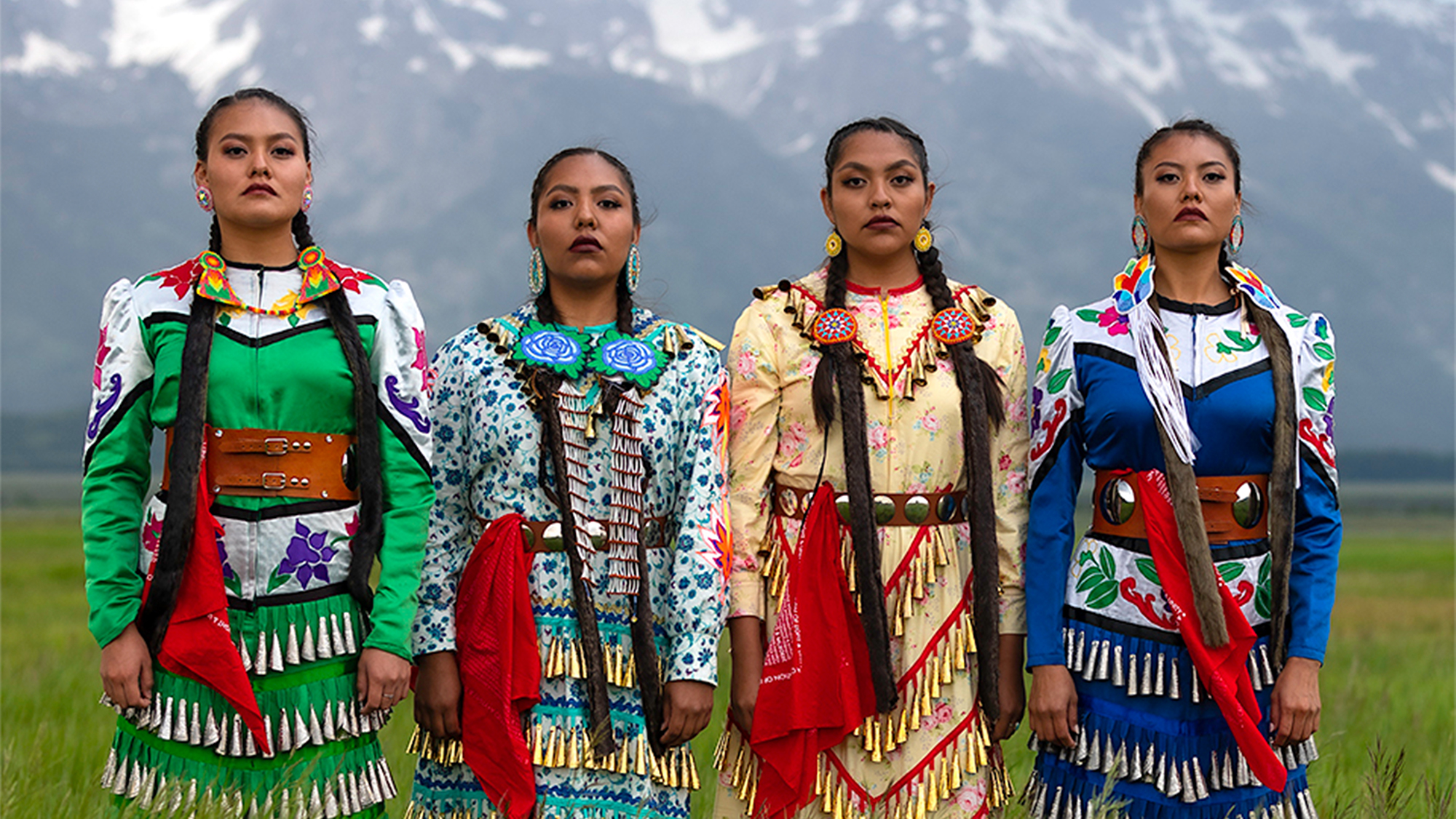 four native women stand shoulder to shoulder in a field with mountains in the background, wearing multi-colored jingle dresses.