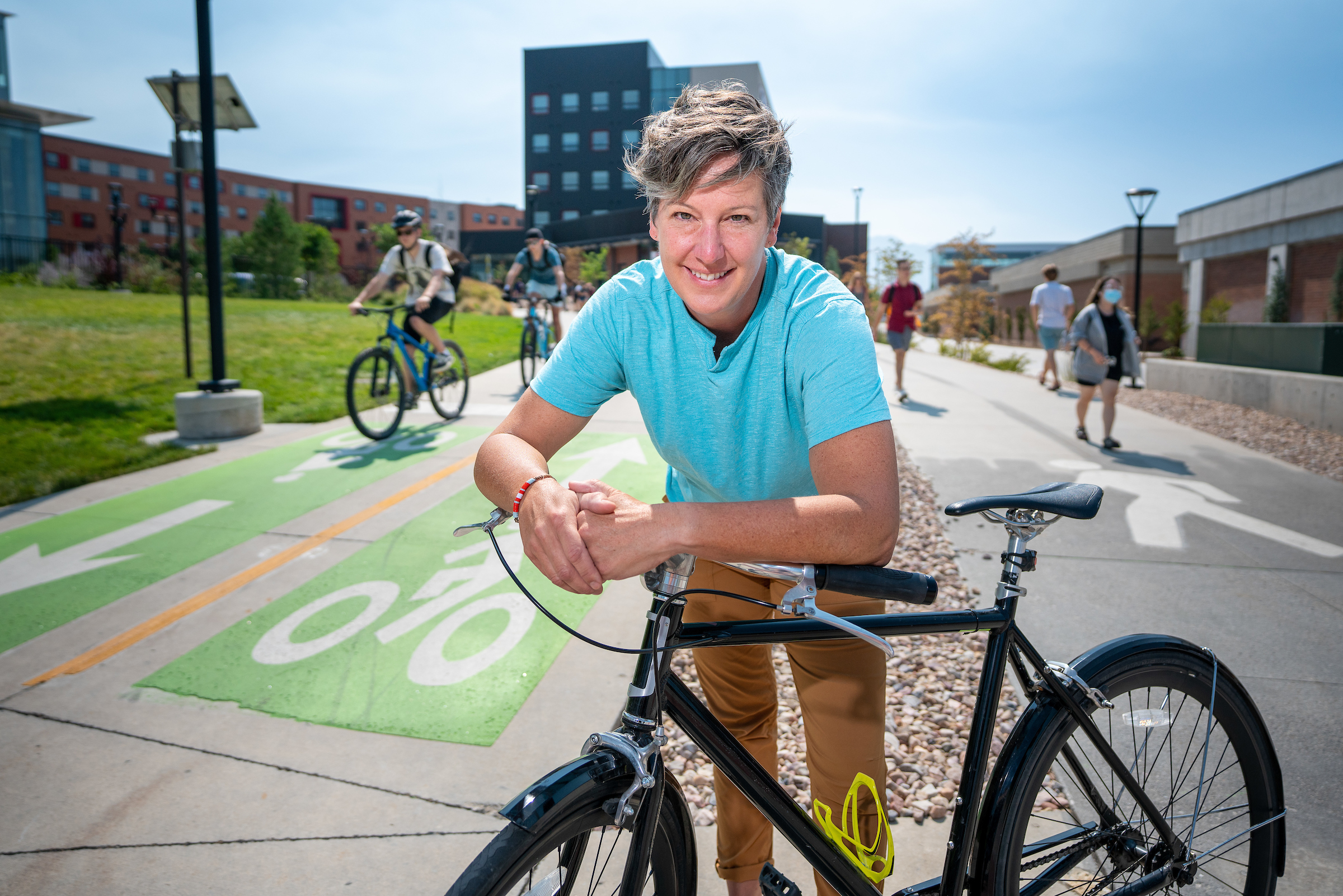Ginger Cannon, the active transportation manager for the University of Utah, poses with her bicycle along a campus bike and pedestrian path.